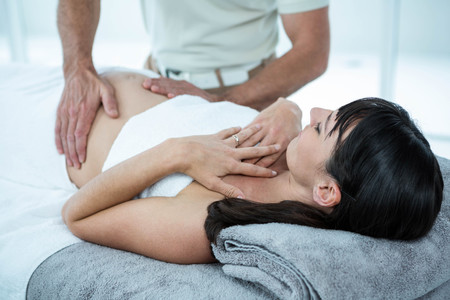 Pregnant woman receiving a stomach massage from masseur at the health spa