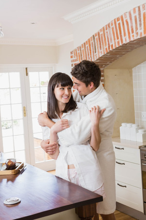 each: Romantic young couple embracing each other in kitchen