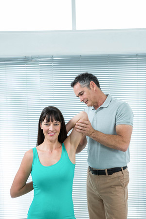 guiding: Physiotherapist guiding pregnant woman with exercise for shoulder and back