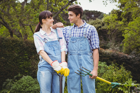Young couple holding shovel and spading fork in garden