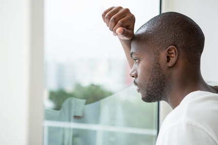 Nachdenklicher Mann aus dem Fenster im Schlafzimmer zu Hause suchen