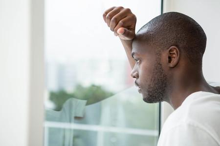 Přemýšlivý člověk dívá z okna v ložnici doma Reklamní fotografie