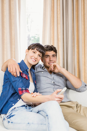 viendo television: Romantic couple at home relaxing on the sofa watching television