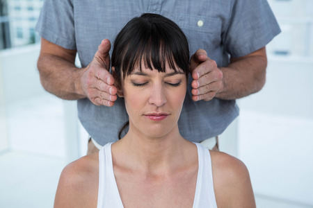 Pregnant woman receiving a head massage from masseur at the health spa Stock Photo