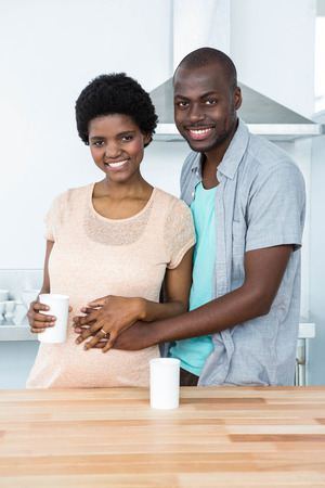 each other: Portrait of pregnant couple embracing each other while having cup of coffee at kitchen Stock Photo