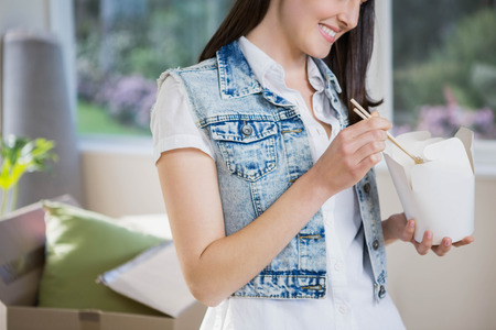 eating noodles: Smiling young woman eating noodles at home Stock Photo
