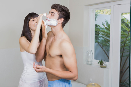 shaving cream: Young woman applying shaving cream on young mans face in the bathroom