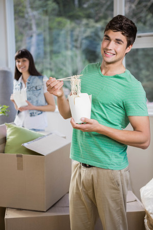 eating noodles: Smiling young man and woman eating noodles at home