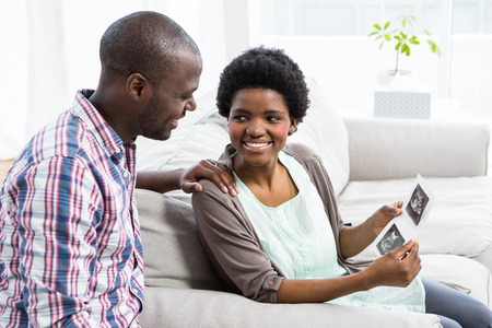ultrasound: Pregnant couple sitting on sofa and looking at ultrasound scan at home