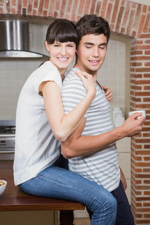 worktop: Young woman sitting on kitchen worktop and embracing man