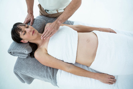 masseur: Pregnant woman receiving a massage from masseur at the health spa Stock Photo