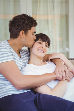 Young Couple Cuddling On Sofa In Living Room Stock Photo, Picture And  Royalty Free Image. Image 53278540.