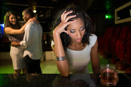 from behind: Unhappy woman sitting at bar counter and couple dancing behind her in bar