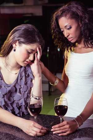 comforting: Woman having drinks and comforting her depressed friend in bar