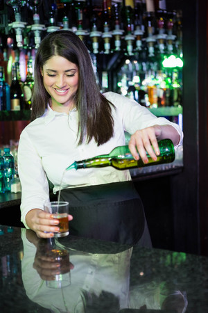 bartending: Pretty bartender pouring whiskey in a glass at bar counter