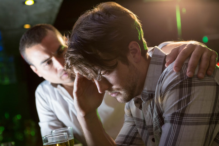 depressed person: Man comforting his depressed friend in bar Stock Photo