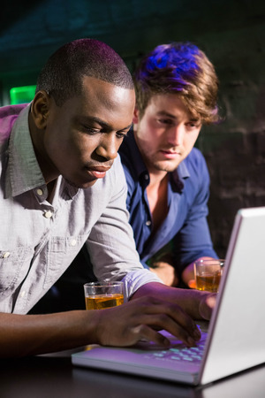 weekend activity: Two men having whiskey and using laptop at bar counter in bar Stock Photo