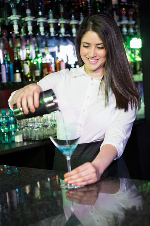 bartending: Pretty bartender pouring a blue martini drink in the glass at bar