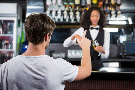 ordering: Man ordering a drink at bar counter in bar Stock Photo