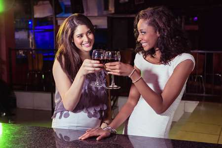 toasting wine: Young women toasting wine glasses at bar counter in bar