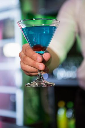 bartending: Bartender serving a blue martini in bar