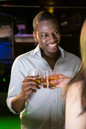 whisky glass: Man smiling while toasting his whisky glass in bar