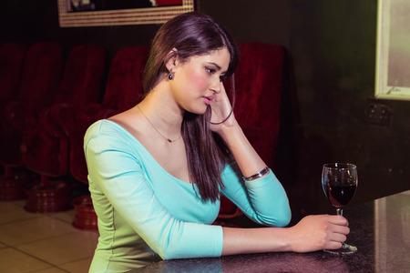 beautiful sad: Thoughtful woman having red wine at bar counter in bar