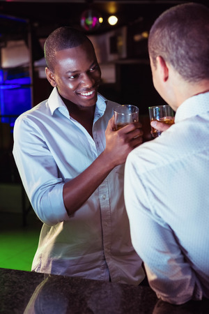 whiskey glass: Two men toasting with glass of whiskey at bar counter in bar