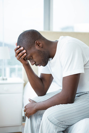hand on forehead: Worried man sitting on sofa with hand on forehead