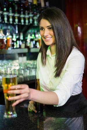 bar counter: Pretty bartender serving beer at bar counter Stock Photo