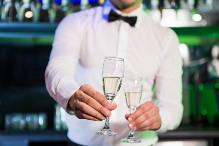 bar counter: Bartender serving glass of champagne at bar counter in bar