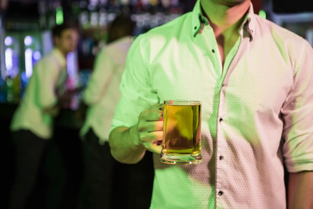 weekend activity: Man posing with glass of beer and friends at bar counter in background Stock Photo