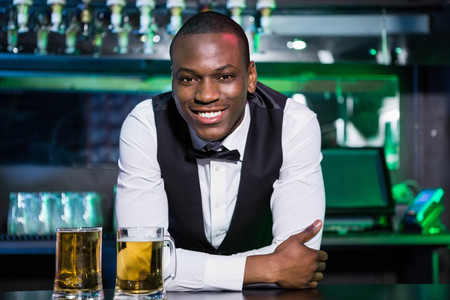 bartender: Portrait of bartender leaning and smiling on bar counter with two glasses of beer in front of him