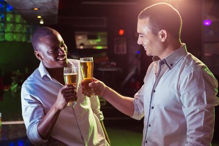 jovenes tomando alcohol: Tostar de dos hombres con un vaso de cerveza en barra Foto de archivo