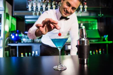 Camarero guarnición de cóctel con cereza en la barra de bar en bar
