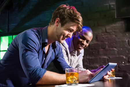 friends at bar: Two men using digital table while having whiskey at bar counter in bar