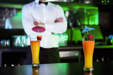bartending: Two glasses of cocktail on bar counter and bartender standing in background