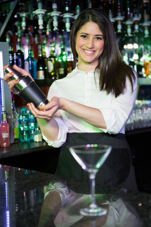 cocktail shaker: Pretty bartender mixing a cocktail drink in cocktail shaker at bar