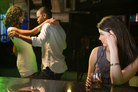 looking behind: Unhappy woman looking at a couple dancing behind her in bar
