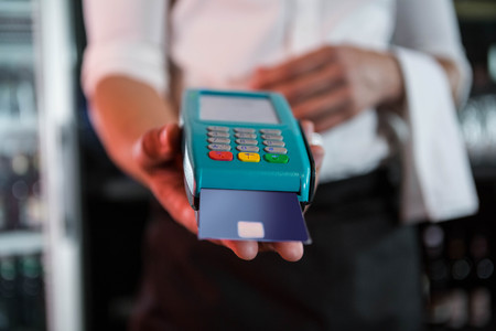 accepting: Bartender accepting a credit card at bar counter in bar