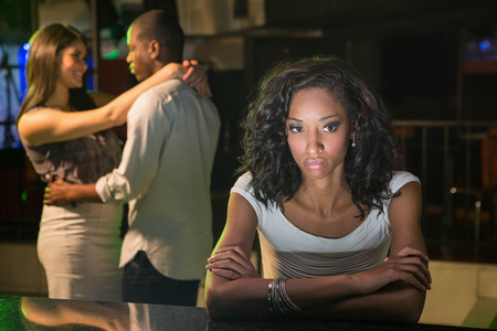 behind: Unhappy woman sitting at bar counter and couple dancing behind her in bar