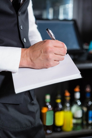 order in: Bartender writing down an order in a bar