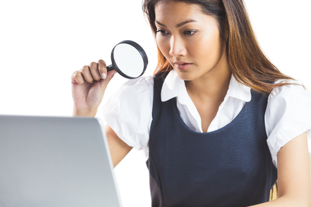 looking through: Businesswoman looking through magnifying glass and using laptop on white background