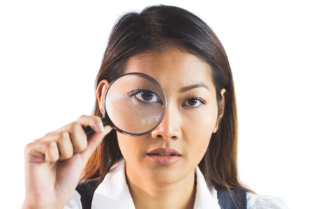 looking through: Businesswoman looking through magnifying glass on white background