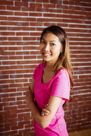 crossing arms: Smiling asian woman crossing arms on brick wall