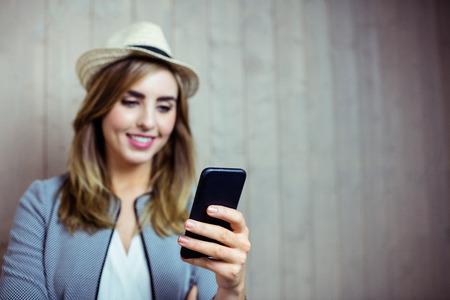 femme blonde: Jolie femme utilisant smartphone sur fond de bois Banque d'images
