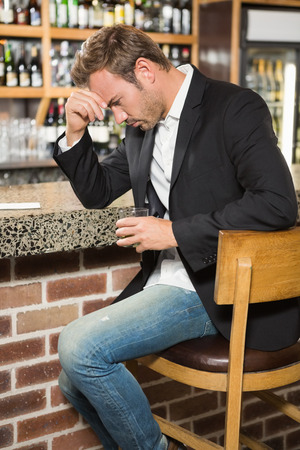 solitariness: Tired man having a whiskey in a pub