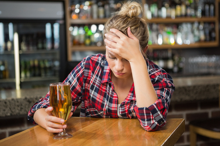 solitariness: Exhausted woman having a beer in a pub