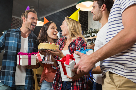 Cute woman celebrating her birthday with a group of friends in a pub