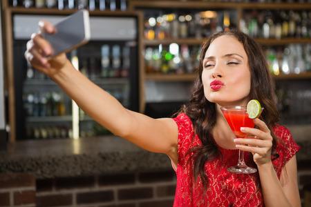 tomando refresco: Pretty woman taking a selfie with her cocktail in a pub Foto de archivo